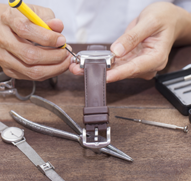 Man with watch repair tools removing back of watch