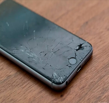 Cracked black iphone on wooden surface