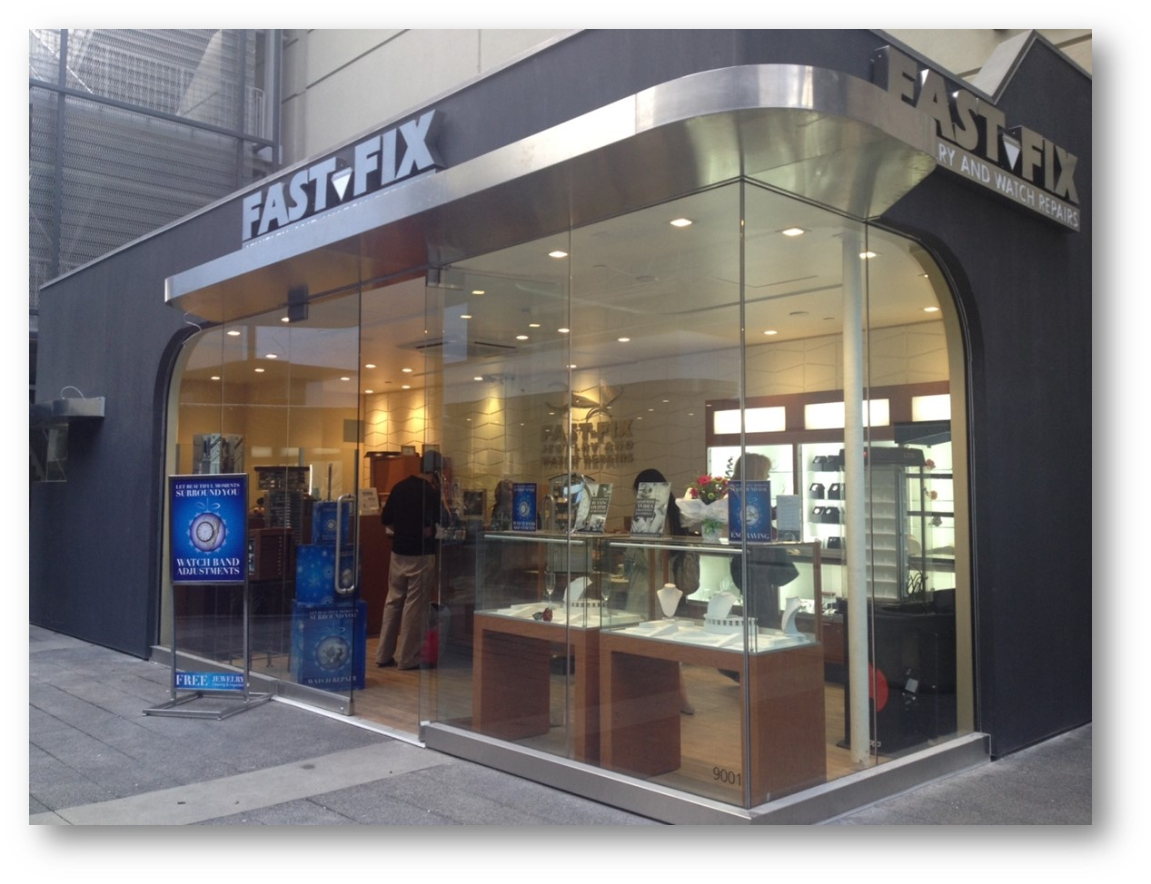 Picture of Fast-Fix store front in Century City Mall, CA. Glass walls that let people see the inside with the jewelry and watches on display.