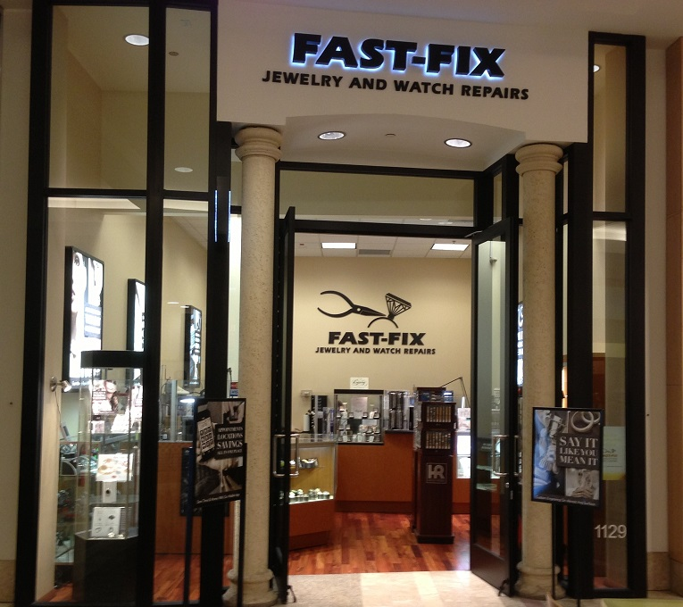 Picture of Fast-Fix storefront at South Center Mall. Two pillars with Fast-Fix Jewelry and watch Repairs logo on top. Windows on the sides that let the customer see through the store.