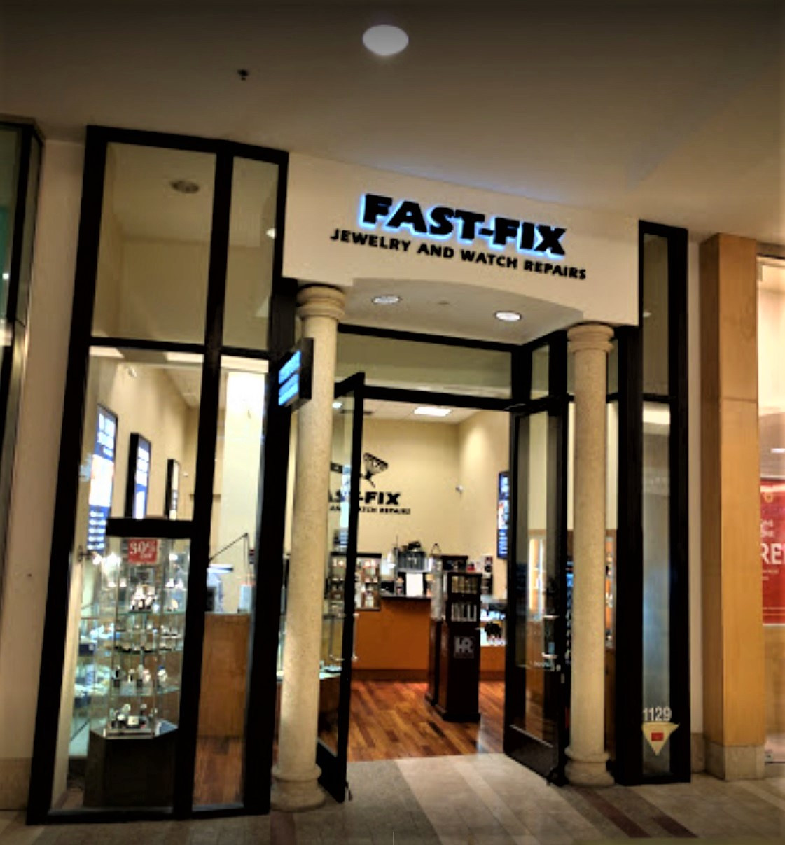 Storefront of Fast-Fix store at South Center Mall. 2 main pillars with logo on top and windows on the sides that let the customer see through the store