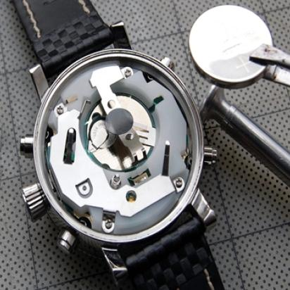 Back of a watch opened, showing the gears, and a battery being approached to it with tweezers.